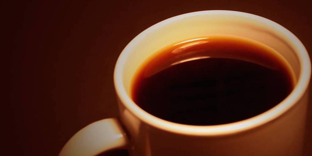 White coffee mug against dark brown background.
